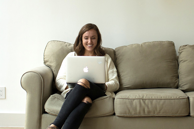 Meghan Easley, MAT Alumni, working on laptop on couch